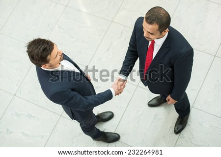 Business partners are shaking hands as a symbol of unity, view from the top. - stock photo
