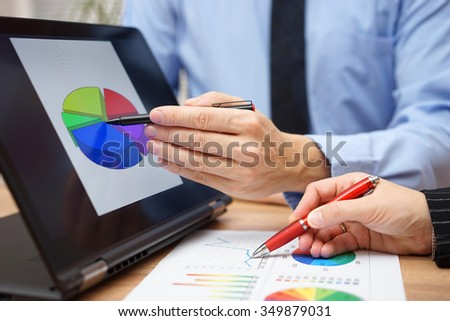 Business partners are working together on statistical data using tablet computer and paper report - stock photo