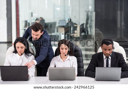 Business partners are working with their manager in a call center. - stock photo