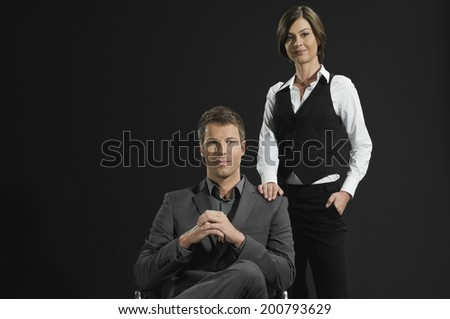Business partners, businesswoman standing businessman sitting