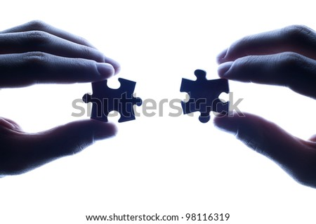 business partners combining puzzle pieces against bright light - stock photo