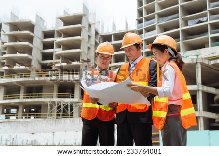 Business partners discussing a blueprint of the building at the construction site - stock photo
