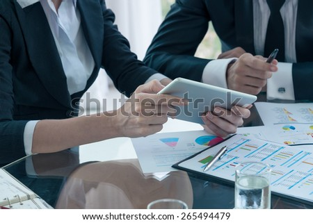 business partners discussing documents and ideas at meeting - stock photo