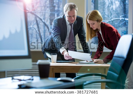 Business partners discussing documents and ideas at meeting. Man and woman in suits working with papers around table in the office. Workspace with computer, coffee and glasses on the foreground.