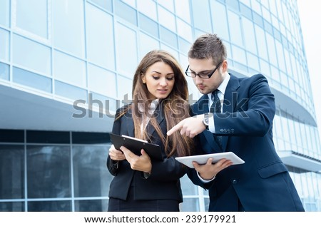 Business partners discussing documents and ideas, standing in front of his office. - stock photo