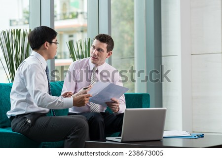 Business partners discussing documents at the meeting - stock photo
