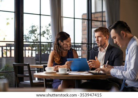 Business partners discussing ideas during lunch in cafe - stock photo