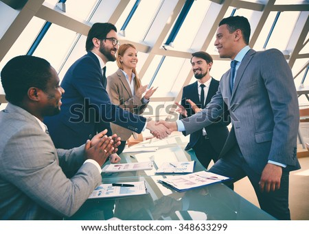 Business partners handshaking after signing contract - stock photo