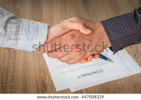 Business partners handshaking over successful conclusion of the business contract