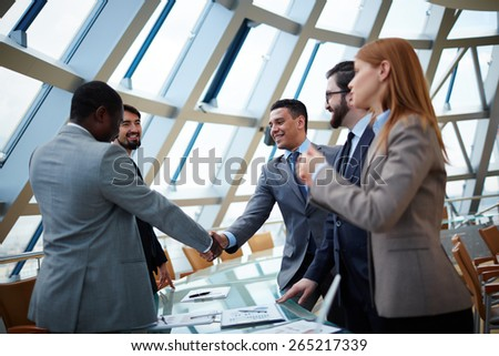 Business partners handshaking upon striking deal in office - stock photo