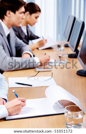 Business partners making notes while sitting in front of computers - stock photo