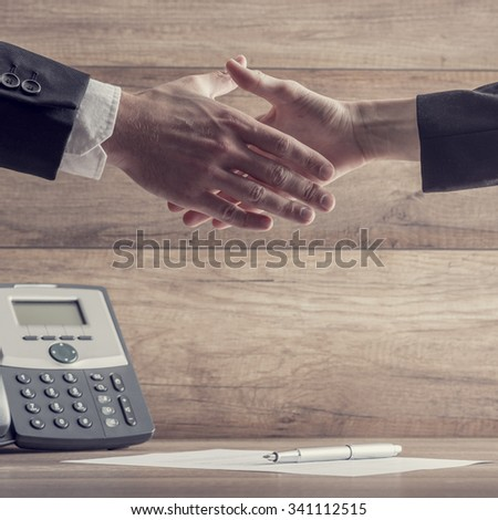 Business partners, man and woman,  shaking hands over a signed contract lying on wooden desk with landline telephone in background. - stock photo