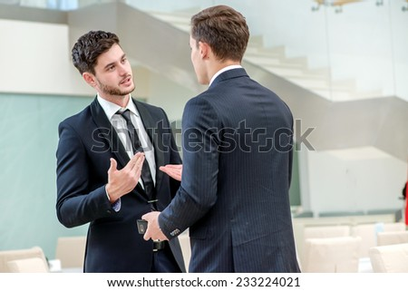 Business partners meeting. Two successful businessman standing in a restaurant and talk to each other. - stock photo