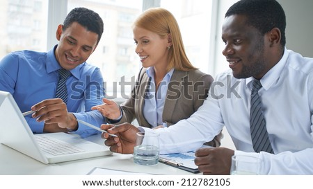 Business partners pointing at laptop screen at meeting - stock photo