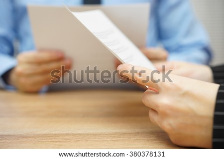 business partners reading and negotiating about legal document - stock photo