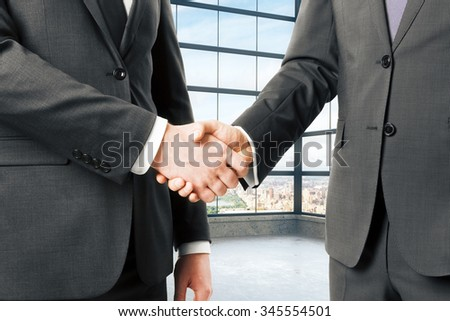 Business partners shake hands in empty loft office - stock photo