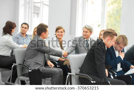 business partners shake hands in the conference room - stock photo