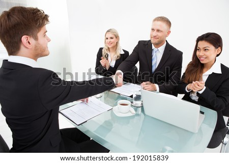 Business partners shaking hands at desk in office - stock photo