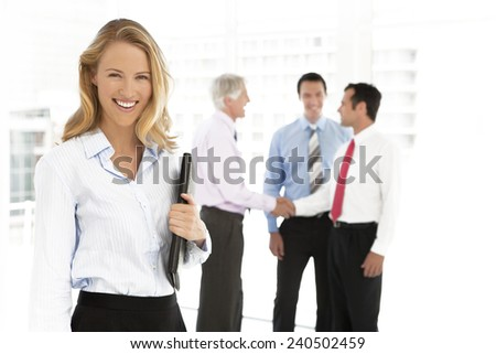 Business partners shaking hands in the background and beautiful young businesswoman looking at camera on foreground - focus on her - stock photo