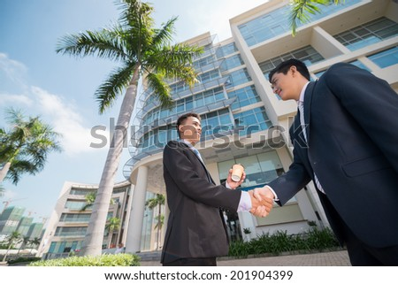 Business partners shaking their hands outdoors - stock photo