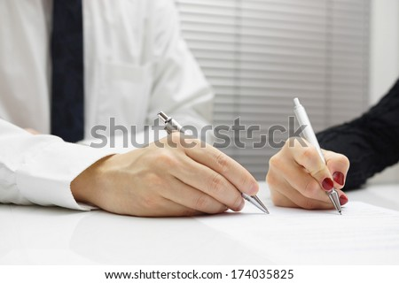 business partners signing a document - stock photo
