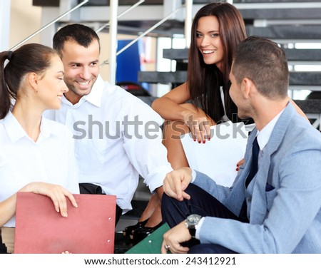 business partners sitting on stairs in office building and discussing work, computer, smiling  - stock photo