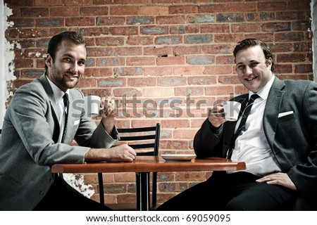 Business partners smile towards camera with coffee in hand