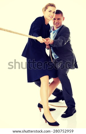 Business partners supporting each other by draging a rope - stock photo
