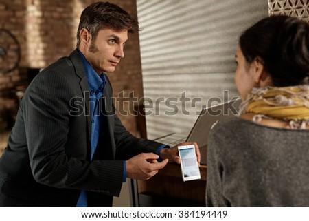Business partners talking, businessman showing something on mobilephone to female partner. - stock photo