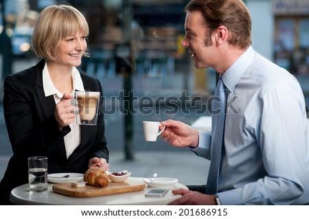 Business partners toasting coffee at cafe - stock photo