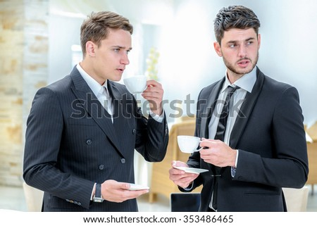 Business partners. Two successful businessman standing in the restaurant and drink coffee while talking to each other. Businessman dressed in formal wear.