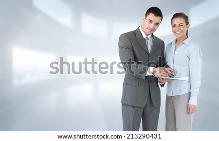 Business partners with clipboard against bright white room with windows - stock photo