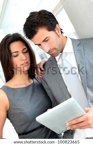 Business partners working in hall on electronic tablet - stock photo