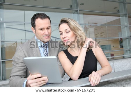 Business partners working on electronic pad - stock photo