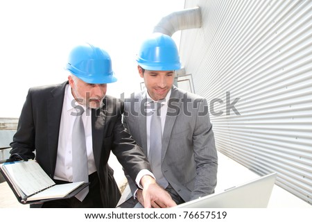 Business partners working on industrial site - stock photo