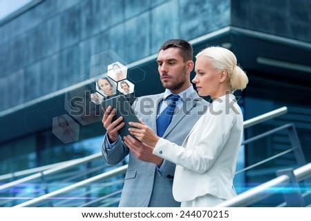 business, partnership, communication, technology and people concept - businessman and businesswoman with tablet pc computer making video call on city street - stock photo
