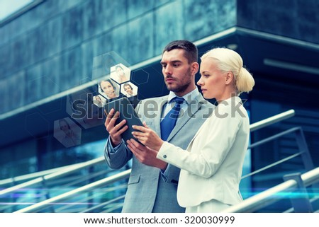 business, partnership, communication, technology and people concept - businessman and businesswoman with tablet pc computer making video call on city street