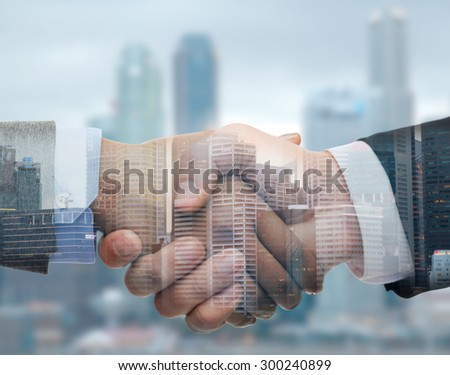 business, partnership, cooperation and gesture concept - businessman and businesswoman shaking hands over city double exposure background - stock photo