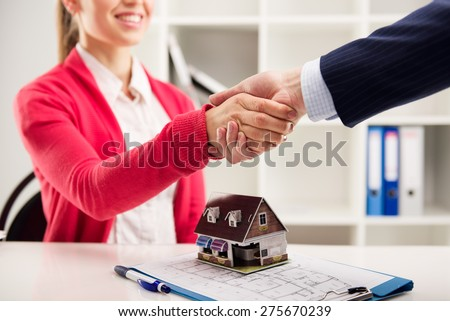 Business partnership. Female house agent greeting customer in the office. Shallow depth of field. - stock photo