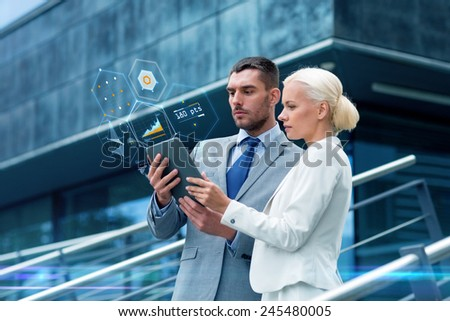 business, partnership, technology and people concept - businessman and businesswoman working with tablet pc computer charts on virtual screens on city street - stock photo