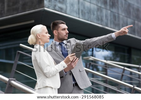 business, partnership, technology and people concept - serious businessman and businesswoman with tablet pc computer over office building - stock photo
