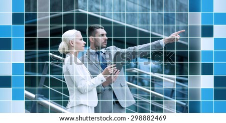 business, partnership, technology, planning and people concept - serious businessman and businesswoman with tablet pc computer over office building over blue squared grid background - stock photo