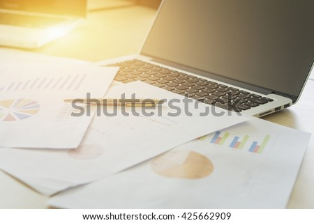 Business,Pen on Office desk table with computer, supplies and chart graph for analyzing financial chart,writing business plan,side view with copy space,vintage color,selective focus - stock photo