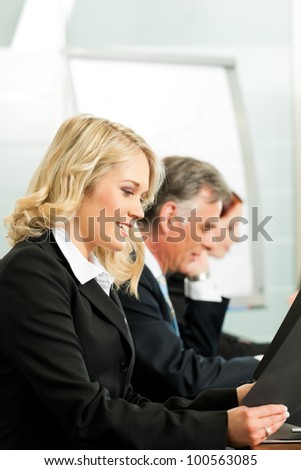 Business people - a team is working in a seminar or workshop - stock photo