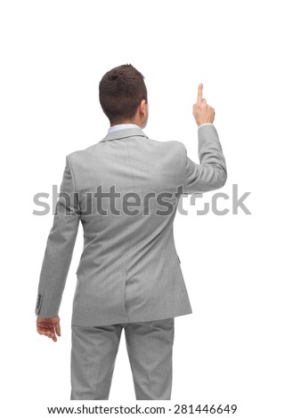 business, people, advertisement and office concept - businessman pointing finger or touching something imaginary from back - stock photo