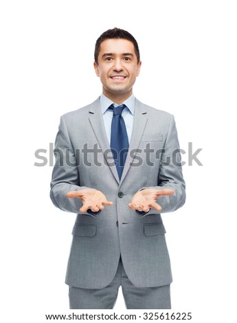 business, people, advertisement and office concept - happy businessman in suit showing or holding something imaginary on empty palms - stock photo