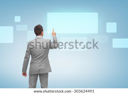 business, people, advertisement and technology concept - businessman pointing finger or touching blank virtual screen over blue background from back - stock photo