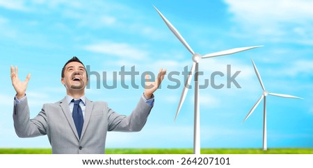 business, people, alternative energy and development concept - happy businessman in suit with raised hands laughing and looking up over blue sky and windmills background