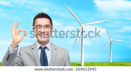 business, people, alternative energy and development concept - happy smiling businessman in eyeglasses and suit showing ok sign over blue sky and windmills background
