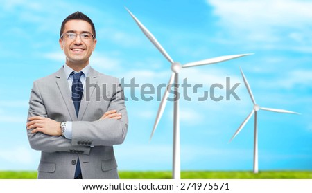 business, people, alternative energy and development concept - happy smiling businessman in eyeglasses and suit over blue sky and windmills background